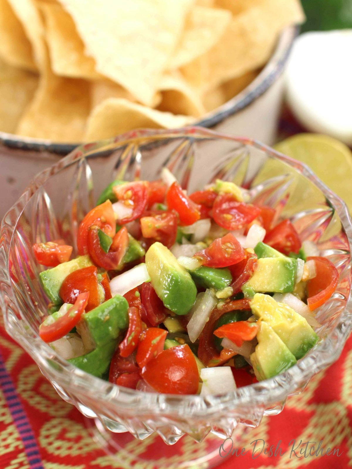 a clear bowl of pico de gallo with avocados and tomatoes next to a bowl of tortilla chips.