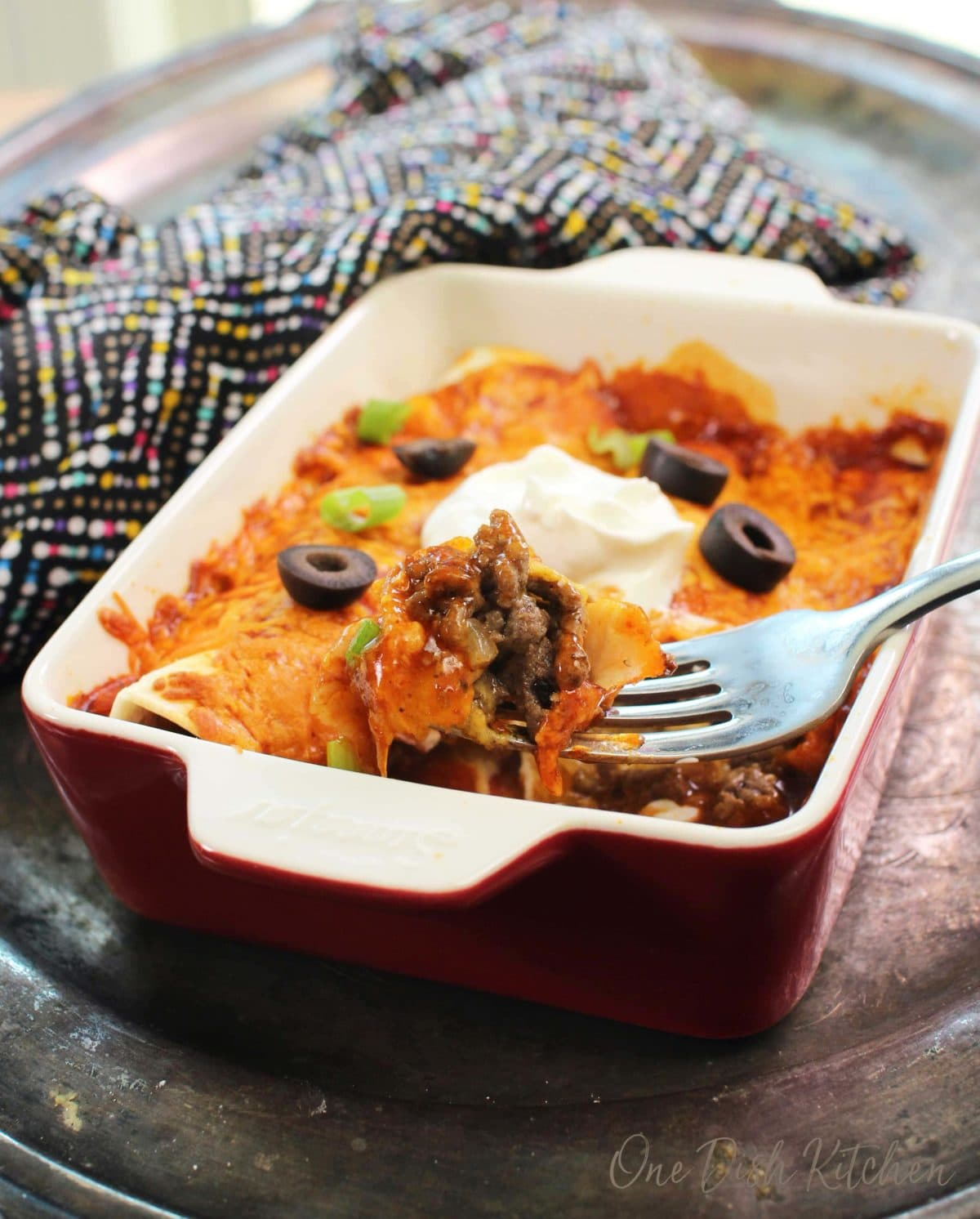 two beef enchiladas in a red dish with a fork on the side of the dish filled with ground beef.