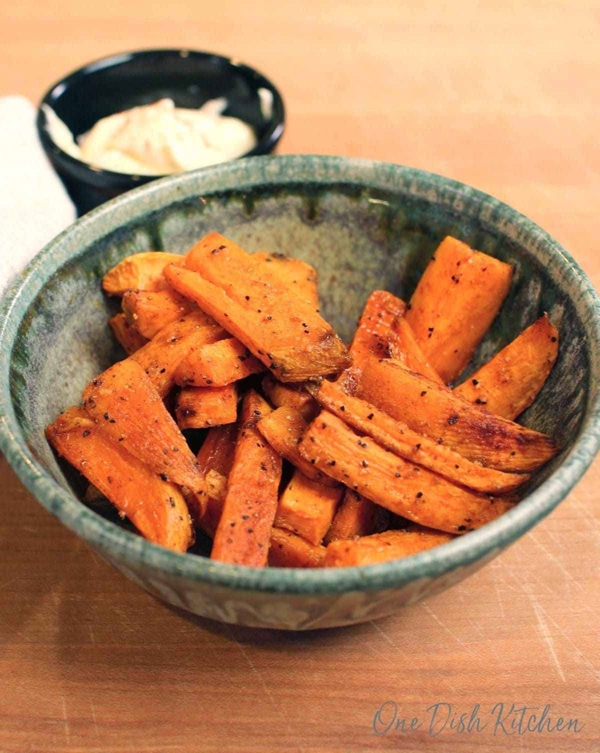 a green bowl filled with sweet potato fries on a brown wood table