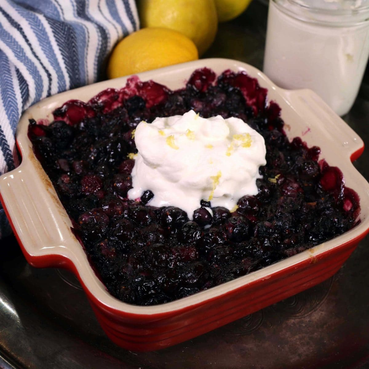 an open faced blueberry pie in a red baking dish next to a blue and white kitchen towel and lemons